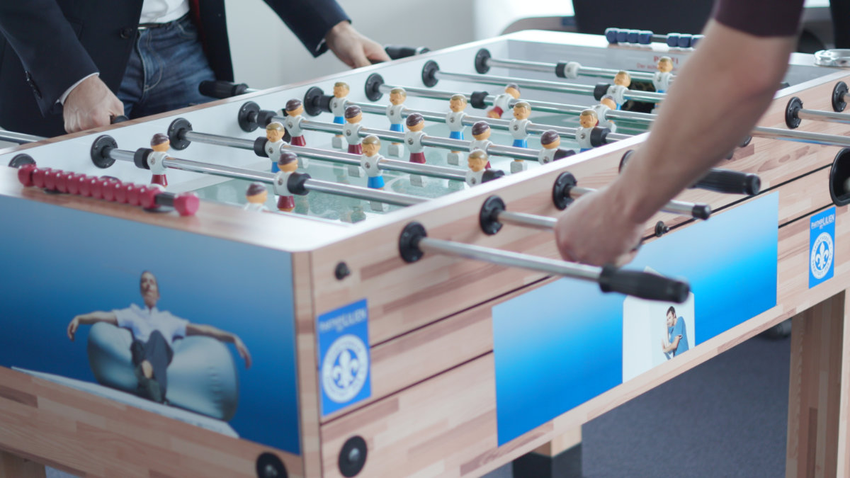 Employees playing at a football table at the toplink office - about toplink